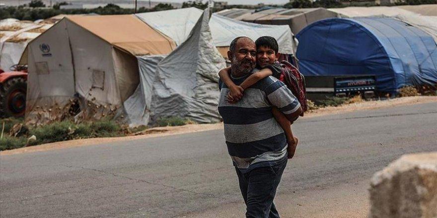 Suriyeli baba engelli oğlunu sırtında taşıyarak okula götürüyor